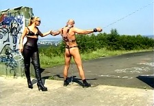 German domina trains chained slave in the outdoors