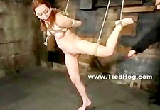 beautifull babe in pink short dress bound in rope with hands behi