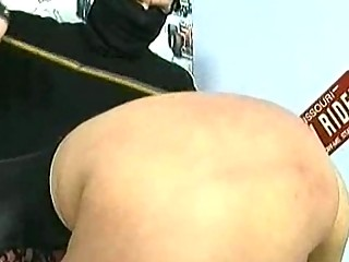 Beautiful slave sitting on a motorcycle is spanked with bamb