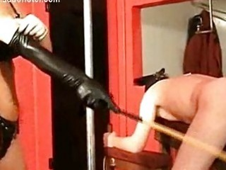 Masked bending over dirty slave is spanked with a wooden sti