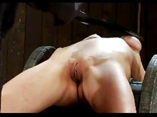 Girl with breast bondage getting tied to wood wheel whipped