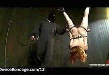 bound suspended redhead gets ass and pussy whipped