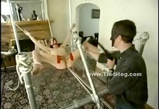 Blonde girl has her nipples bound in clamps while being tied up on a glass table